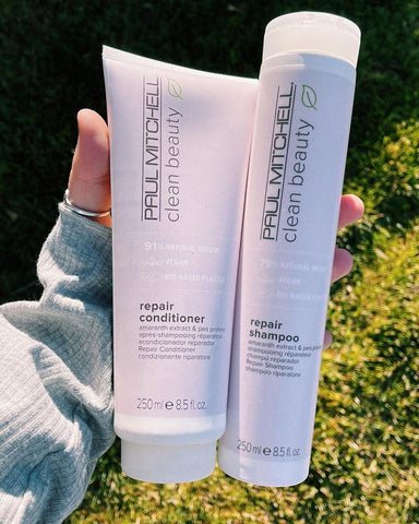 Hand holding Paul Mitchell Clean Beauty Repair shampoo and conditioner. These bottles are made of bio-based packaging.