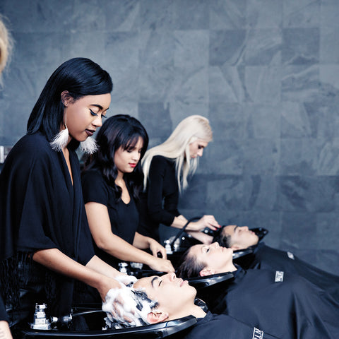 girls washing clients hair at basin in Paul Mitchell hair salon