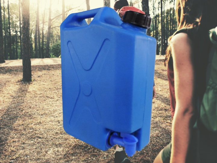 Couple hiking in the woods with a blue Pionee rplastcis water tank in the foreground