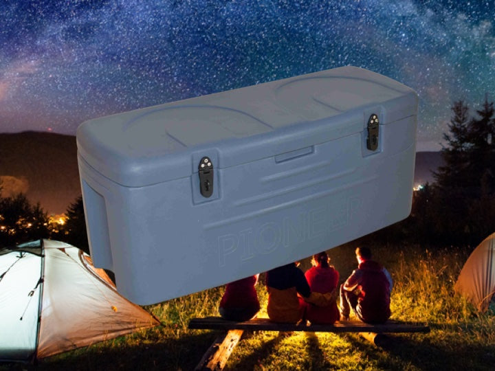 Family camping in  the evening sitting around a camp fire with a white Pioneer plastics cooler box in the foreground