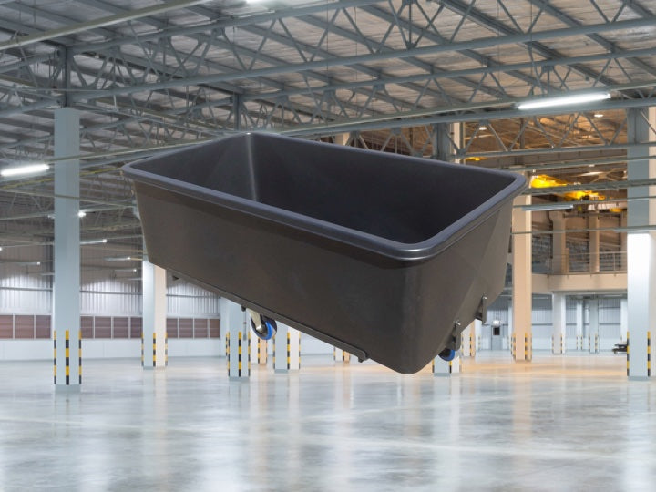 Warehouse space with a black Pioneer Plastics roller bin in the foreground