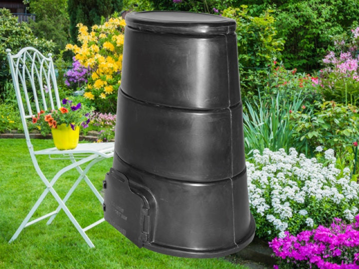 Beautiful garden with a black Pioneer plastics compost bin in the foreground