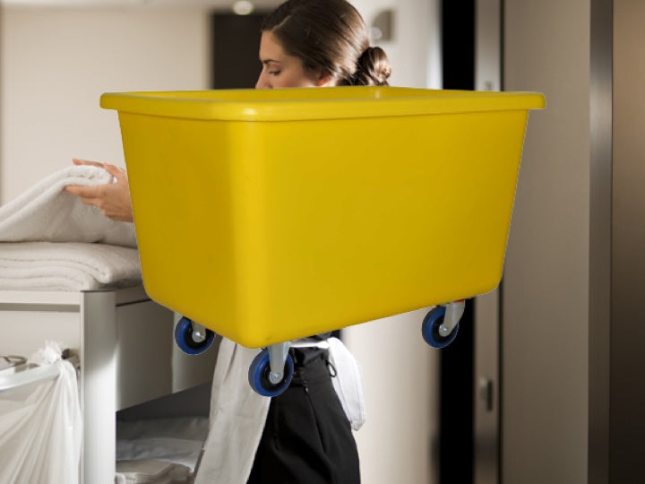 Hotel Cleaning services folding towels with a yellow Pioneer plastics bin with wheels in the foreground