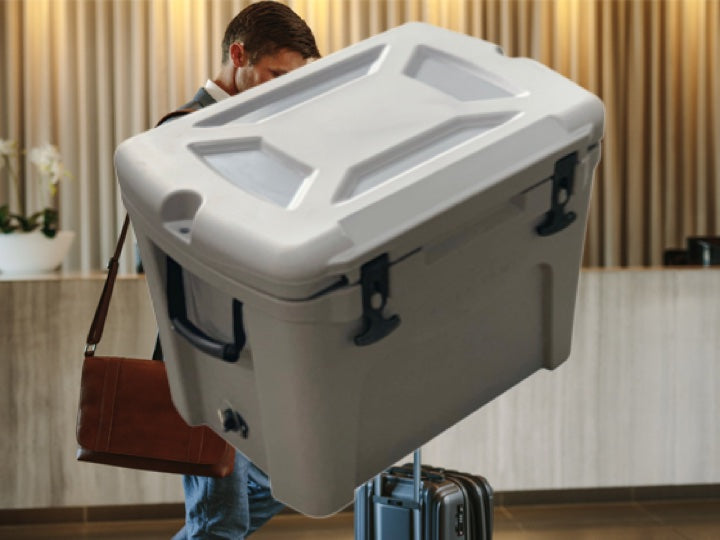 Business man checking into a hotel with a white Pioneer Plastics cooler box in the foreground