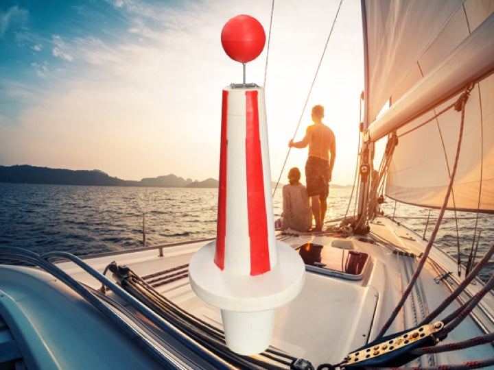 A coouple sailing on a yacht with a red and white Pioneer plastics Iala Safe Water Mark bouys in the foreground