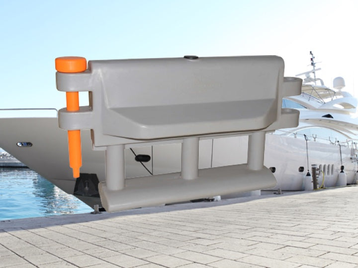 A yacht docked with a white and orange Pioner plastics hyacinth barrier in the foreground