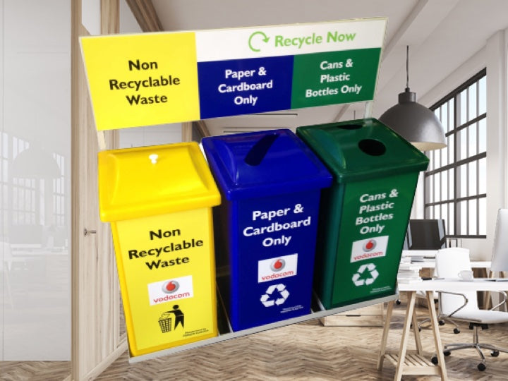 Office setting with a yellow, blue & green Pioneer plastics recycle bins in the foreground