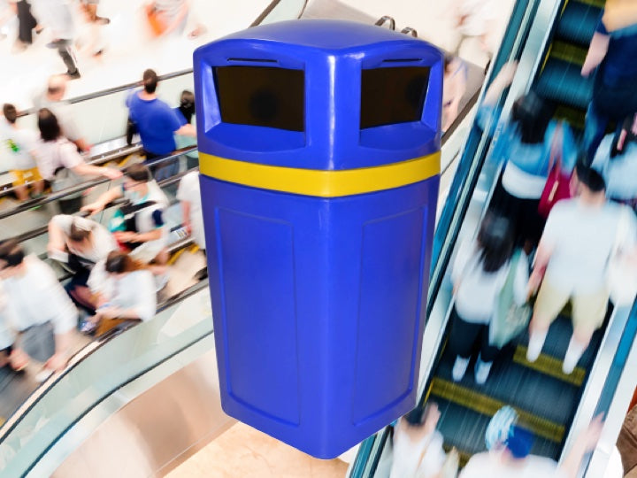 Faced paced image of shoppers in a mall on escalators with a blue and yellow Pioneer plastics litter bin in the foreground