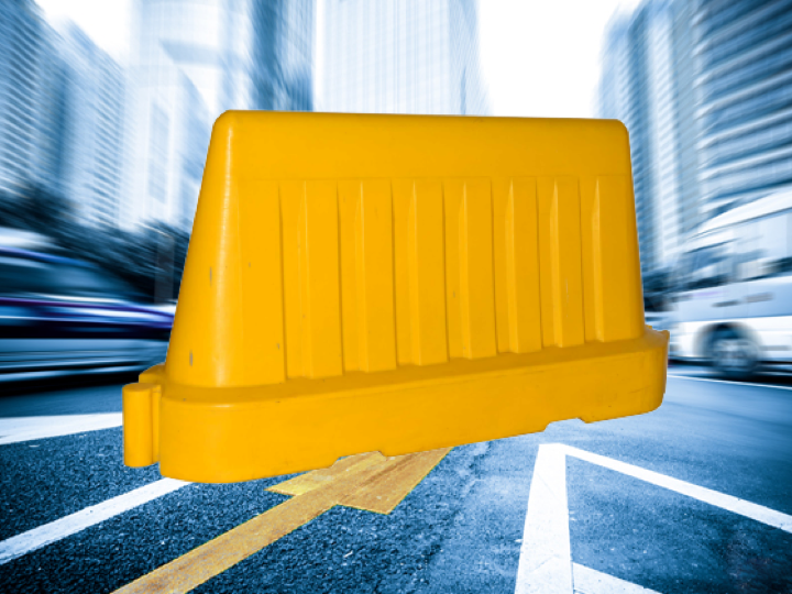 Fast paced picture of a city road with a yellow Pioneer plastics nesting road barrier in the foreground