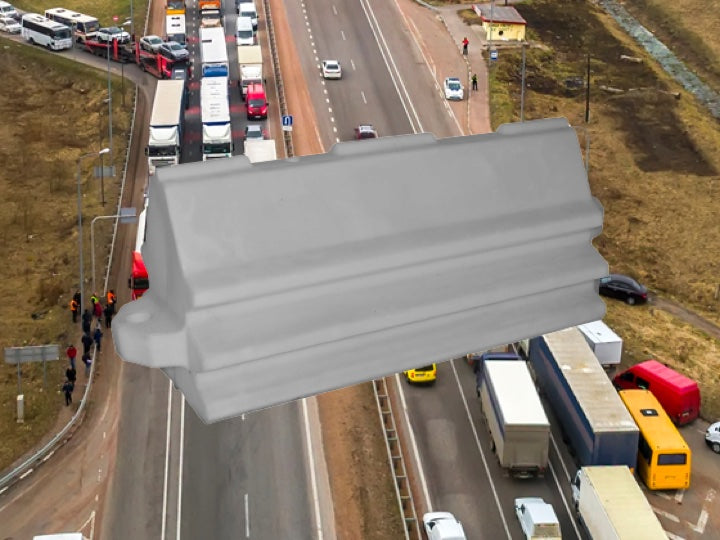 road with a traffic jam with a white Pioneer plastics pedestrian road barrier in the foreground