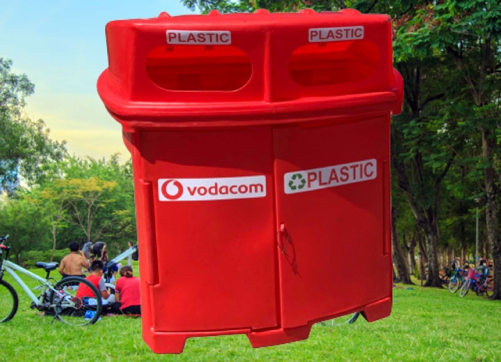 people sitting in the park with a red Pioneer plastics 1000L recycle bin in the foreground