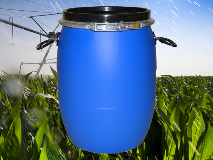 Farming field being watered witha blue Pioneer plastics Chemical drum in the foreground