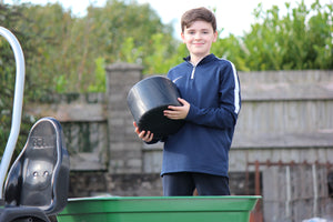 Round plastic bale being held by kid