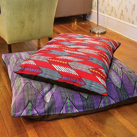Two custom pet bed pillows on a hardwood floor