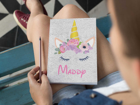 Girl sitting with expressiffy's personalized Sequin Unicorn notebook