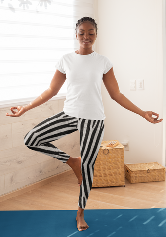 A woman wearing a pair of zebra leggings doing a tree pose