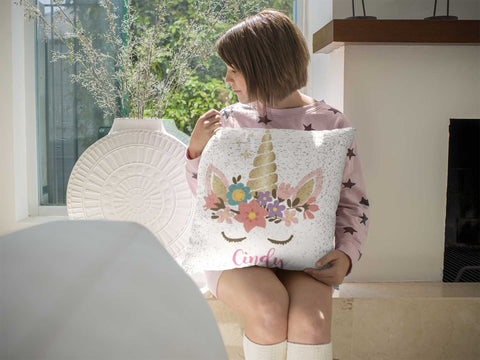 Girl holding an Expressiffy unicorn sequin pillow
