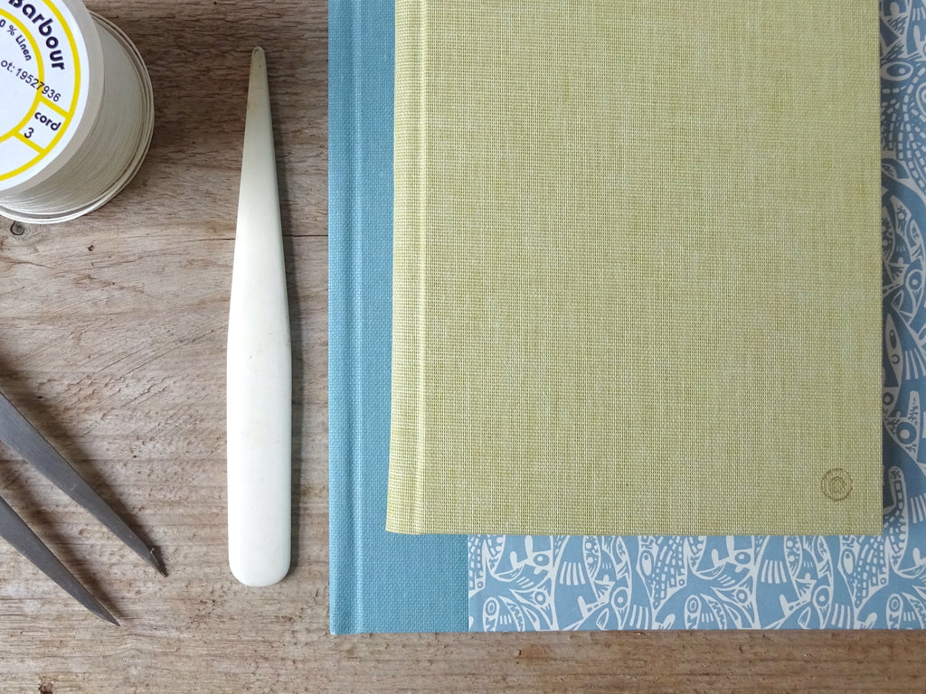 2 hand bound books by Megan Stallworthy with tools and thread