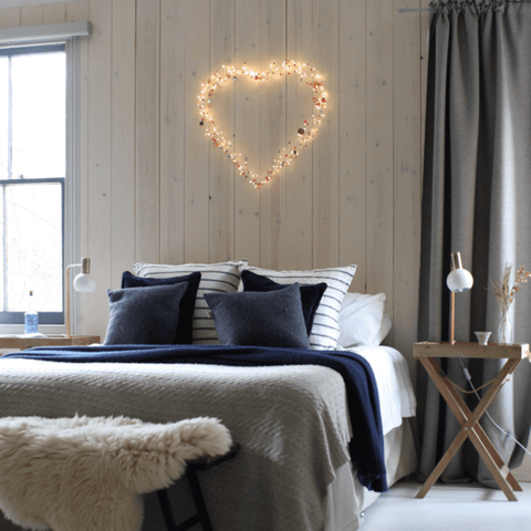 Boho heart wall light over a bed in a bedroom