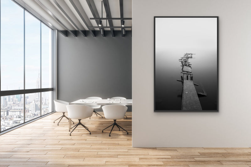 White Framed picture of a black and white photo of a jetty.