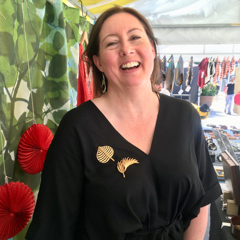 Audra Daws-Knowles demonstrating how to wear a brooch with a sponge Canopy Market