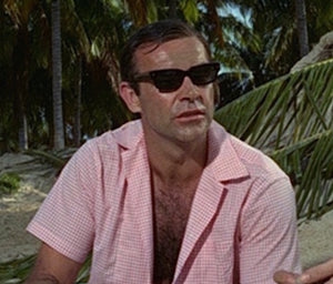 sean connery wearing a shirt whilst sitting on a beach