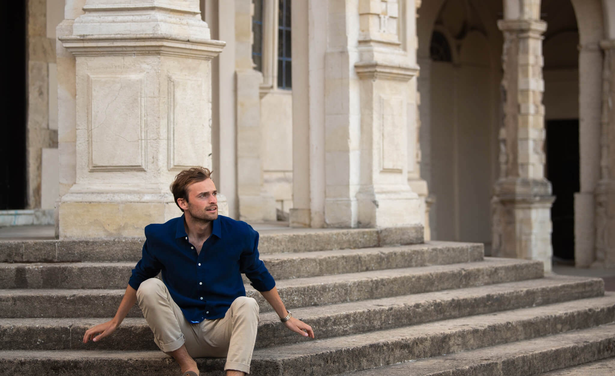 Harry, our model, sitting on steps whilst modelling a navy blue hemp shirt. hemp clothing by babble & hemp. location is London. the fabric of the shirt is 100% hemp.