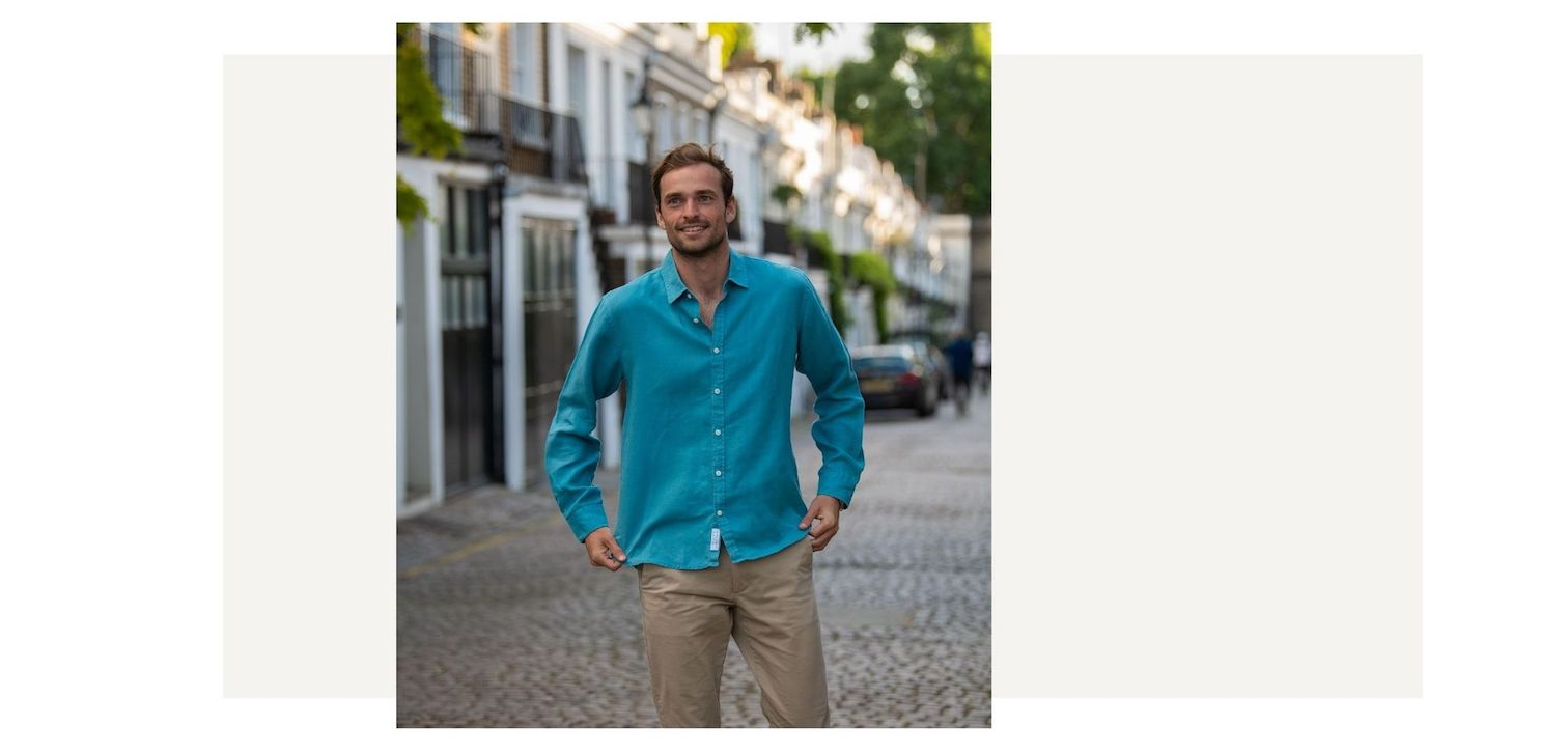 a model wearing a petrol blue hemp shirt whilst walking down a street. the colour of the fabric is blue. the fabric is made from 100% hemp