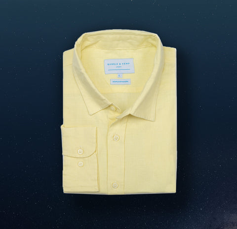 a dawn yellow hemp shirt on a navy blue background. colour of the shirt is yellow and the fabric is 100% hemp.