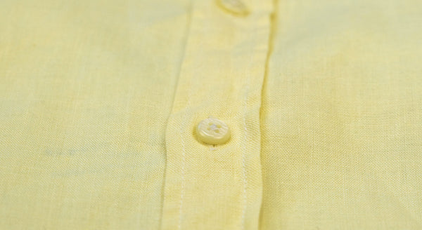 a close-up details photo of the fabric and buttons of a yellow hemp shirt.