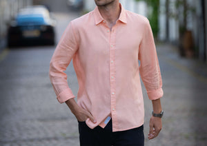 an editorial shot of the model wearing bahama peach hemp shirt. colour pink/peach. fabric is 100% hemp.