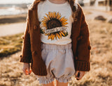Little girl wearing a sunflower shirt and bloomers