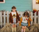 Two little girls wearing sweaters and bloomer shorts