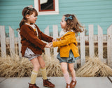 Two little girls twirling wearing sweaters and bloomer shorts