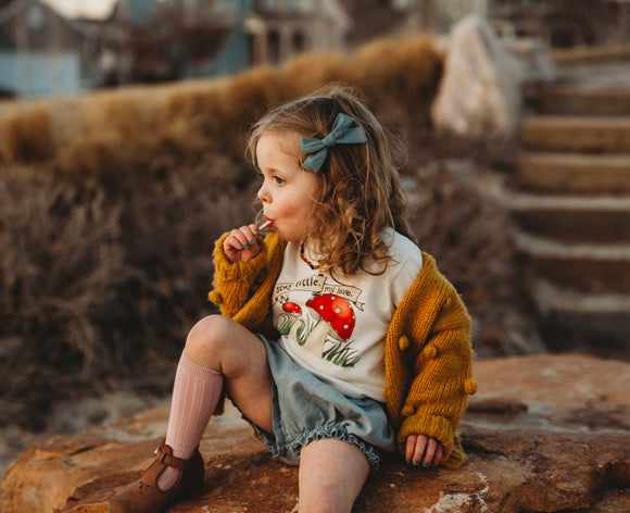 Little girl sitting wearing blue bloomers and a tee shirt