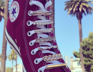 Gold shoelace charms with rhinestones and pearls on a dark red Converse All Star hightop sneaker