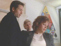 Photograph of David Duchovny and Gillian Anderson on a set for the X FIles featuring a painting by Gregg Simpson in the background of alchemy and magic symbols. The episode is from Season 2 of he X-Files.