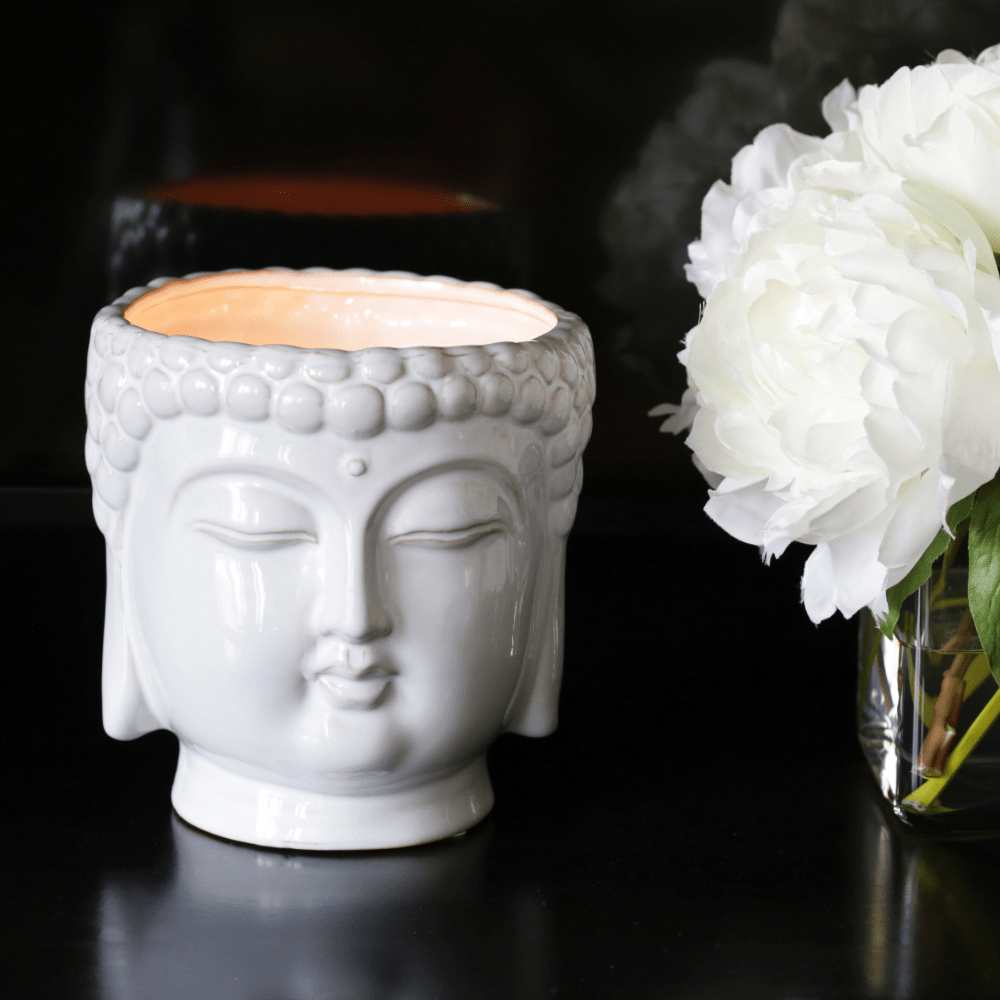 white ceramic buddha head candle next to bouquet of flowers