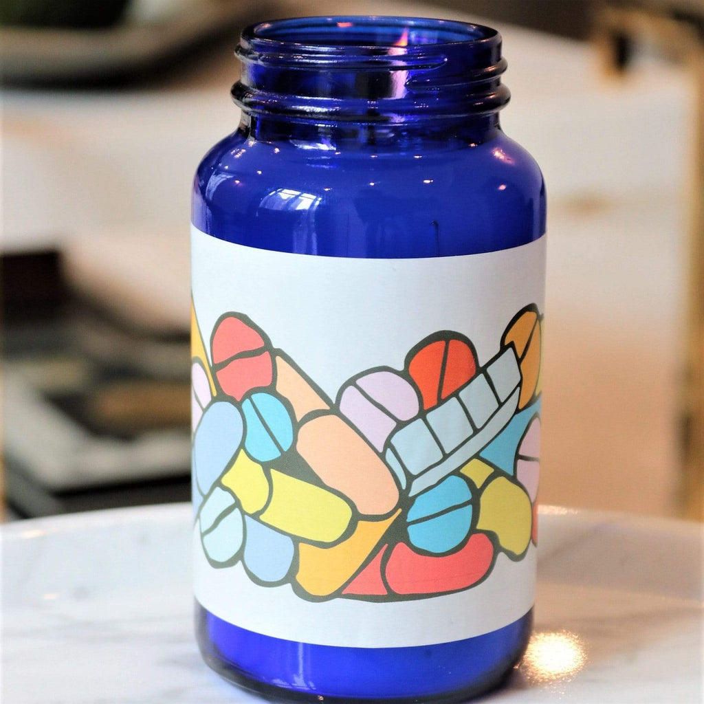 blue glass pill bottle candle with white sticker and colorful pills with white wax and one wick