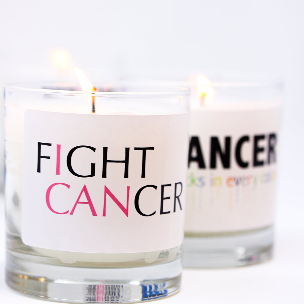 Thompson Ferrier clear glass vessel scented candle with label on it about fighting cancer
