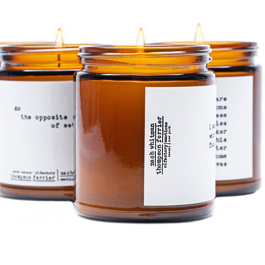 brown glass jar with lid and white label on it with white soy wax and a single cotton wick