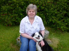 Photograph of Judith Mackay, owner of Tweed Bag Creations and her dog Molly in the front garden of 29 Sheshader
