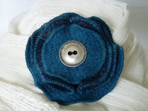 Pretty Harris Tweed brooch/ corsage with two plain teal and two folded small multi check layers finished with a decorative pewter button. The brooch is sewn on to a clear backing button and brooch clip.