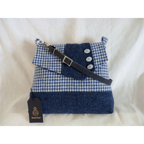 Harris Tweed Attleborough shoulder/ crossbody bag in blue and white houndstooth check with blue/ black mix bands and flap panel finished with three decorative buttons. This bag has a plain black lining with an inner zipped pocket, it has a magnetic snap fastener under the flap and a clip on navy leather strap which is adjustable to approximately 120 cm (47 inches) not including clips and rings and as with all my bags, it has the Harris Tweed orb mark label on the inside.