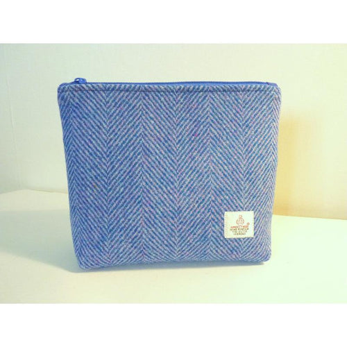 Handmade Harris Tweed cosmetic bag in blue herringbone fabric with hints of pink, a black waterproof lining and zip closure