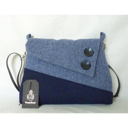 Sedgeford shoulder/ crossbody bag in plain navy and chalky blue Harris Tweed with flap finished with 2 feature buttons. This bag has a plain navy lining with an inner zipped pocket, it has a magnetic snap fastener under the flap and a clip on navy leather strap which is adjustable to approximately 120 cm (47 inches) not including clips and rings and as with all my bags, it has the Harris Tweed orb mark label.
