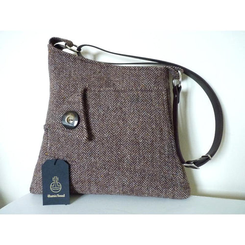This lovely slim but sizeable bag made in brown herringbone Harris Tweed has a sloping topline with a decorative and functional front pocket with a large button trim