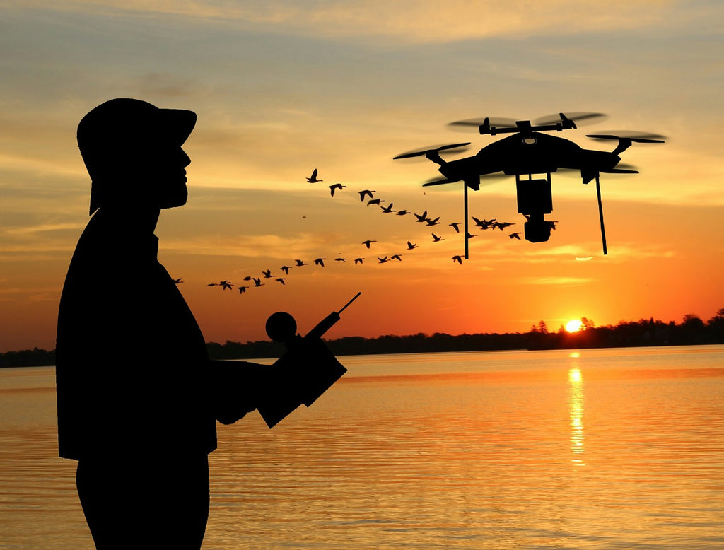 A man controlling a drone at a wonderful sunset next to each other.