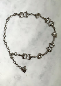 Silver-tone chain belt with horse-head detail.