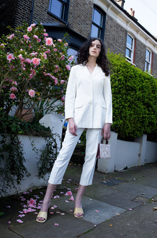 Rosalind Jana wears white single-breasted cropped length trousers suit for Human Sea Vintage